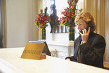 Woman talking on telephone behind hotel reception desk
