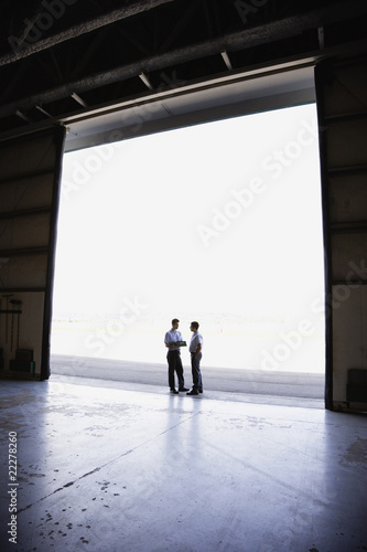 Two male workers in hangar doorway