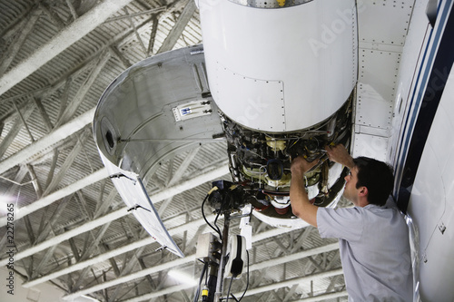 Middle Eastern repairman working on airplane engine