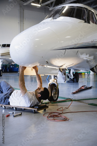Repairman fixing airplane