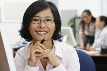 Portrait of Asian businesswoman holding pen