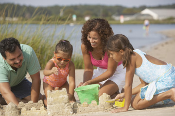 Hispanic family making sandcastle at beach