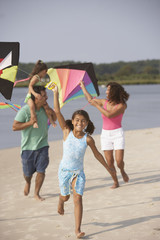 Hispanic family flying kites on beach