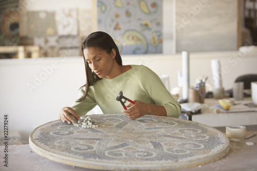 African mosaic artist working in studio