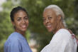 African female nurse and senior female patient smiling outdoors