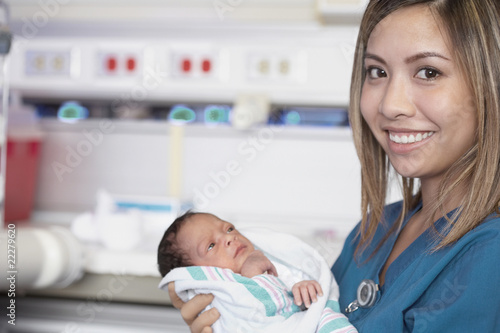 Asian female nurse smiling and holding newborn baby
