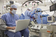 Doctor using laptop in operating room with surgery in background