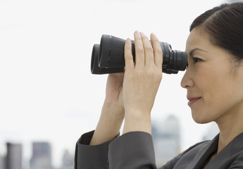 Profile of Asian businesswoman looking through binoculars