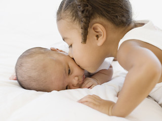 African girl kissing newborn baby sibling