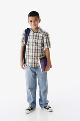 Studio shot of Hispanic boy carrying backpack and books