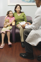 Doctor talking to Hispanic mother and daughter in waiting room
