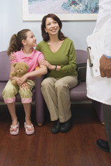 Hispanic mother and daughter talking to doctor in waiting room