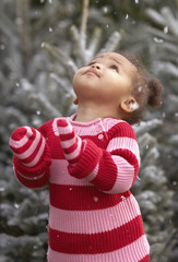 African baby girl standing in falling snow