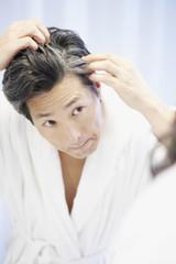 Asian man looking at gray hair in mirror