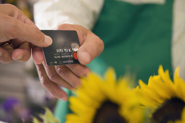 Customer paying with credit card at florist