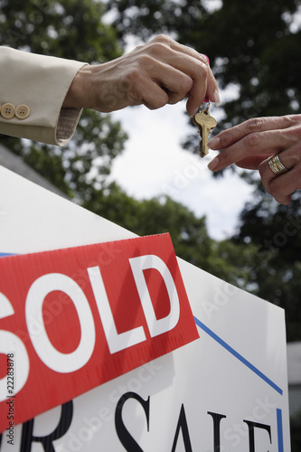 Real estate agent handing house keys to buyer