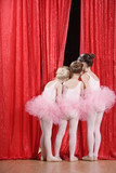 Multi-ethnic girls in ballet outfits peeking through curtain