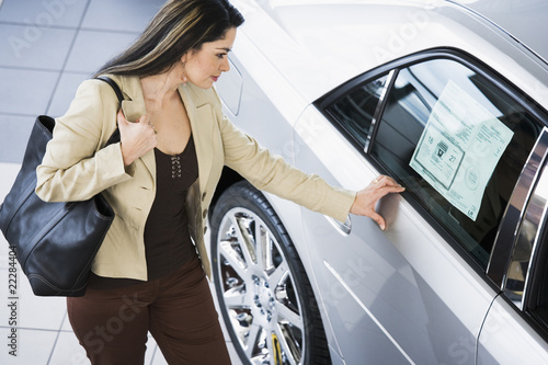 Hispanic woman looking at new car