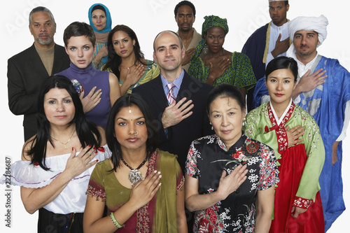 Multi-ethnic people in traditional dress holding hand on heart