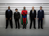 Multi-ethnic businessmen and superhero in police line up