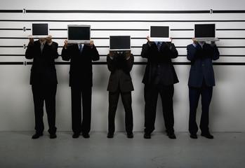 Multi-ethnic businessmen holding laptops in police line up