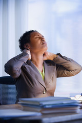 African businesswoman rubbing neck