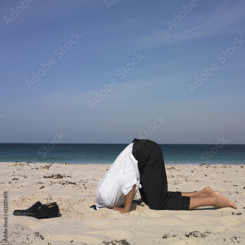 Hispanic businessman with head in sand