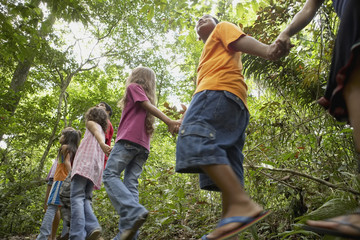 Hispanic children exploring woods