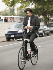Hispanic businessman riding bicycle