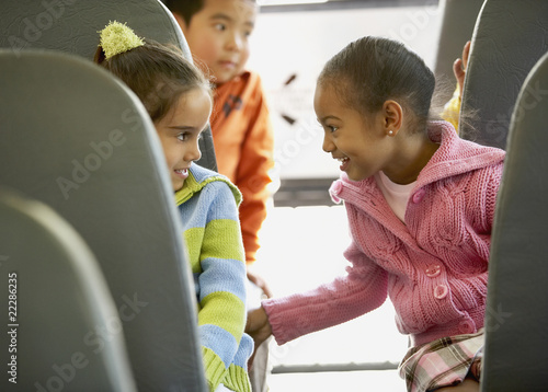 Multi-ethnic girls talking on school bus