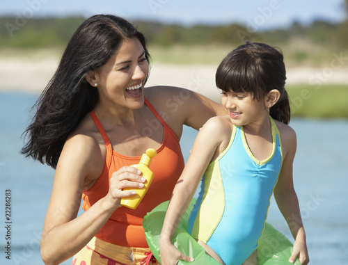 Hispanic mother applying sunscreen on daughter