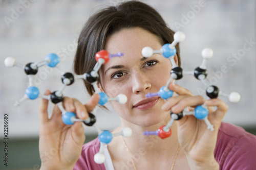 Hispanic woman holding molecular model