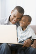 African American father and son looking at laptop