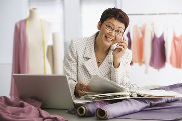 Asian female clothing designer talking on cell phone