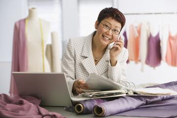 Asian female clothing designer talking on cell phone