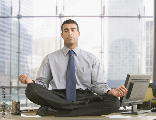 Hispanic businessman meditating on desk