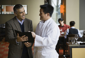 Restaurant manager and chef discussing menu