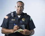 African American male police officer writing ticket