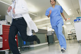 Medical professionals running in hallway