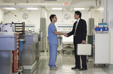 Hispanic medical professional shaking hands with businessman