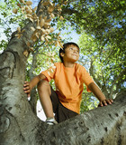 Hispanic boy climbing tree