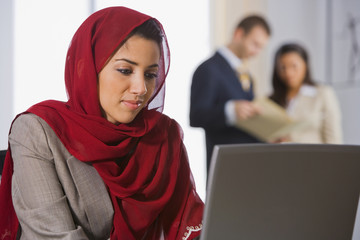 Middle Eastern businesswoman looking at laptop