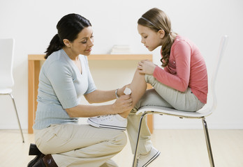 Hispanic mother putting bandage on daughter's leg
