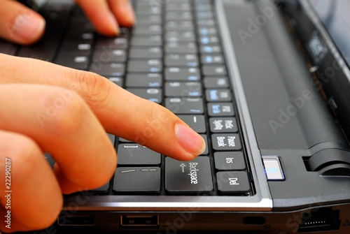 Finger pressing backspace button on laptop