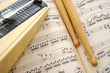 Music score, drum sticks and metronome