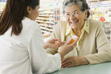 Senior Hispanic woman discussing medication with pharmacist
