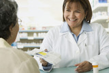 Hispanic female pharmacist handing medication to customer