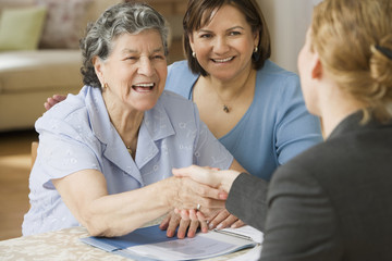 Senior Hispanic woman shaking hands with businesswoman