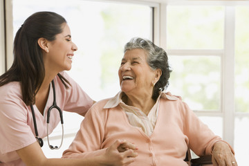 Senior Hispanic woman and nurse laughing