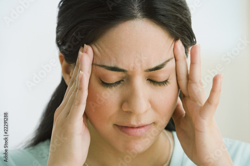Hispanic woman rubbing forehead